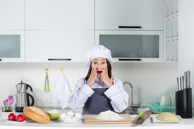 Vista frontal da chef feminina surpresa, em pé de uniforme atrás da mesa, com uma tábua de cortar legumes e pão na cozinha branca