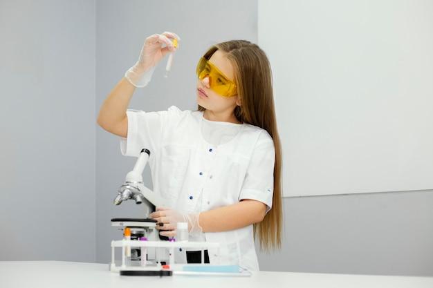 Vista frontal da cientista com microscópio e tubo de ensaio