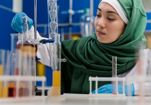Vista frontal da cientista feminina com hijab em laboratório