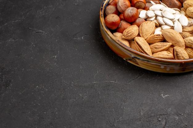 Vista frontal da composição de amendoins e outras nozes na superfície escura