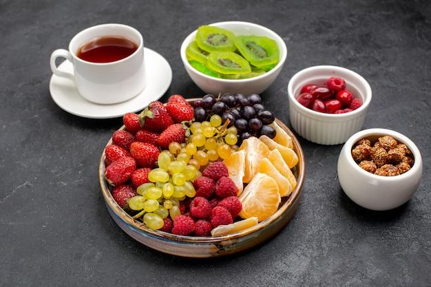Vista frontal da composição de frutas com diferentes frutas frescas com uma xícara de chá na mesa cinza-escuro
