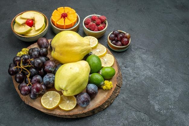 Vista frontal da composição de frutas diferentes frescas e maduras em fundo cinza escuro frutas maduras maduras frescas saúde