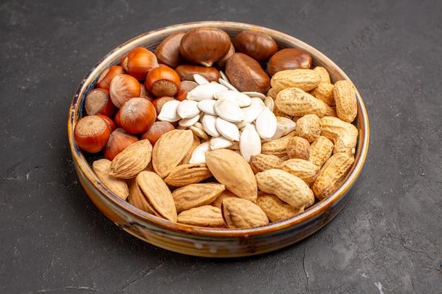 Vista frontal da composição de nozes, amendoins, avelãs e outros na superfície escura
