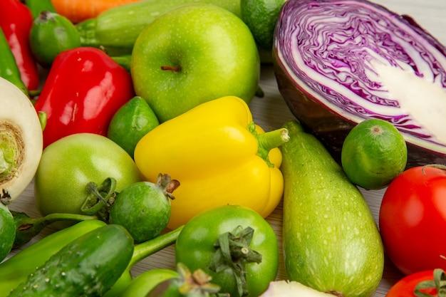 Vista frontal da composição vegetal com frutas no fundo branco dieta salada saúde foto colorida madura