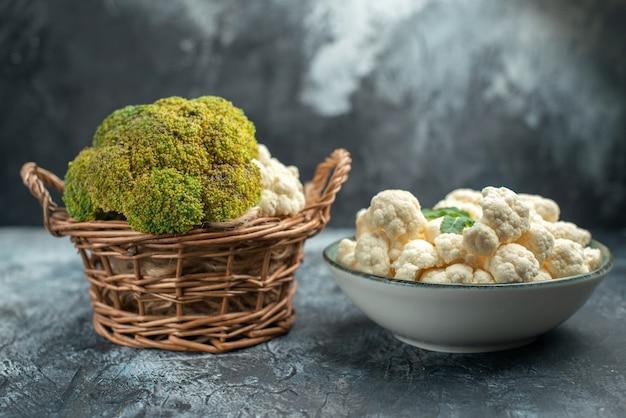 Vista frontal da couve-flor fresca dentro da cesta e prato em superfície cinza claro
