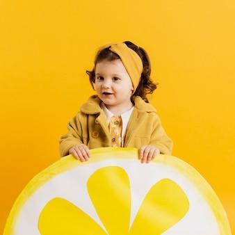 Vista frontal da criança adorável posando com decoração de fatia de limão