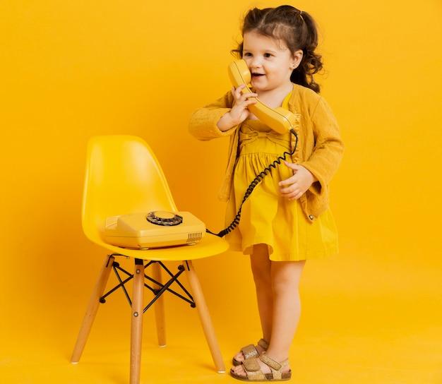 Vista frontal da criança adorável posando enquanto segura o telefone