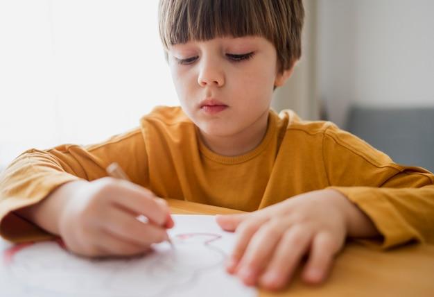 Vista frontal da criança desenhando em casa