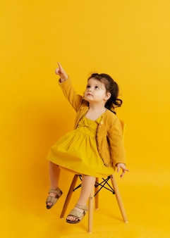 Vista frontal da criança posando enquanto está sentado na cadeira e apontando para cima