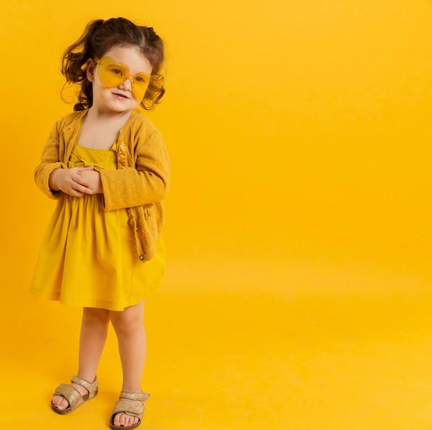 Vista frontal da criança posando enquanto usava óculos de sol