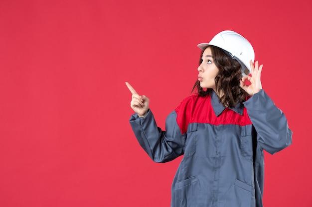 Vista frontal da curiosa construtora de uniforme com capacete e fazendo gesto de óculos apontando para cima sobre fundo vermelho isolado