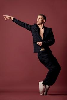 Vista frontal da dança masculina posando enquanto mostra o movimento clássico do pé em pé