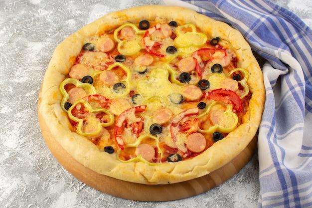 Vista frontal da deliciosa pizza de queijo com azeitonas salsichas e tomates na mesa cinza