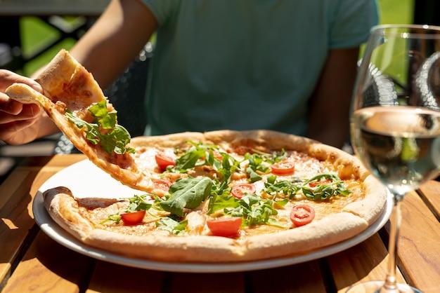 Vista frontal da deliciosa pizza na mesa de madeira