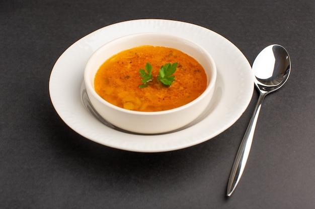Vista frontal da deliciosa sopa dentro do prato com a colher na mesa escura