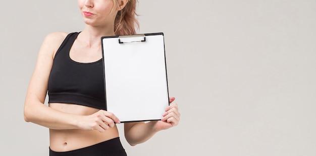 Vista frontal da desportiva mulher segurando o bloco de notas