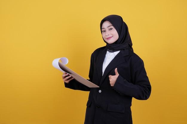 Vista frontal da elegante empresária segurando a prancheta e sorrindo bem em amarelo