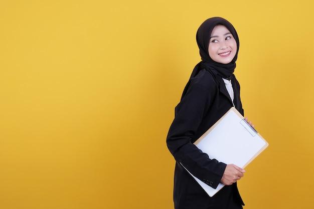 Vista frontal da elegante empresária segurando a prancheta em amarelo