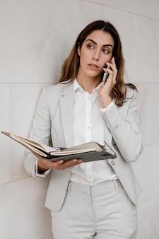 Vista frontal da elegante mulher de negócios com agenda falando ao telefone