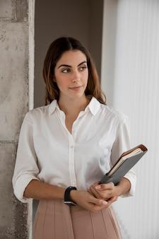 Vista frontal da elegante mulher de negócios com agenda