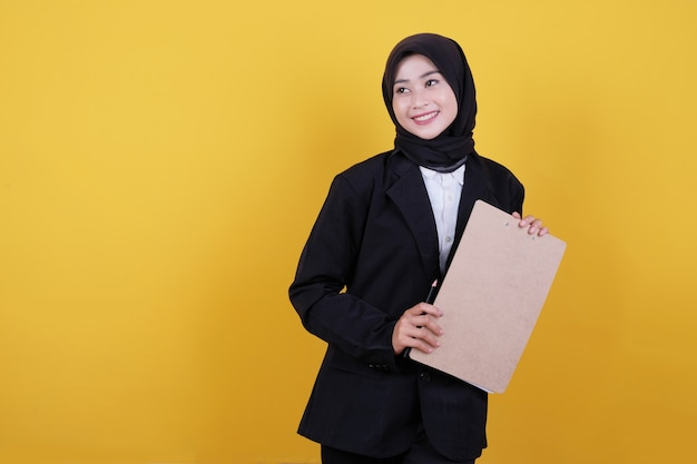 Vista frontal da elegante mulher de negócios segurando a prancheta e sorrindo em amarelo