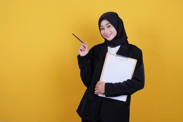 Vista frontal da elegante mulher de negócios segurando a prancheta, sorrindo e apontando para o lado esquerdo em amarelo