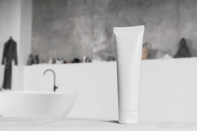 Vista frontal da embalagem em branco do produto cosmético no banheiro