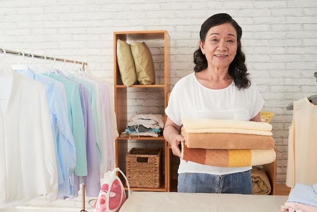 Vista frontal da empregada asiática em pé com toalhas na lavanderia