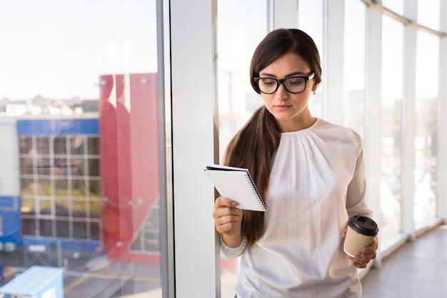 Vista frontal da empresária com café e notebook