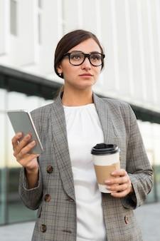 Vista frontal da empresária com café e smartphone ao ar livre