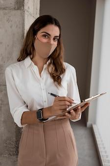 Vista frontal da empresária com máscara segurando a prancheta
