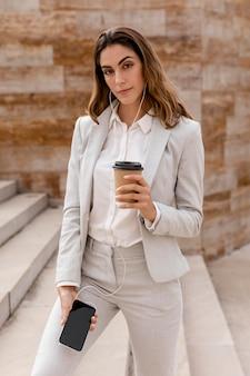 Vista frontal da empresária com smartphone e café