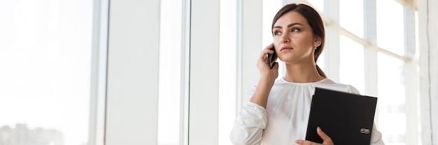 Vista frontal da empresária falando ao telefone com espaço de cópia