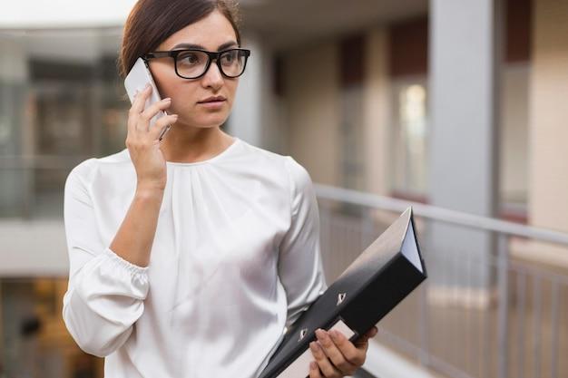 Vista frontal da empresária falando no telefone enquanto segura a pasta