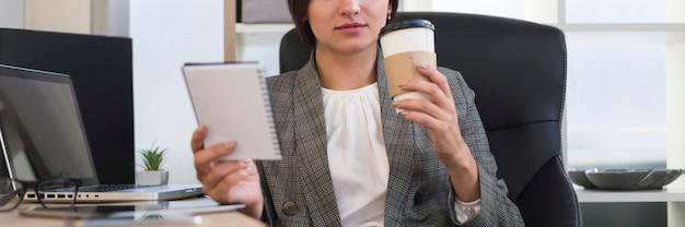 Vista frontal da empresária no escritório tomando café