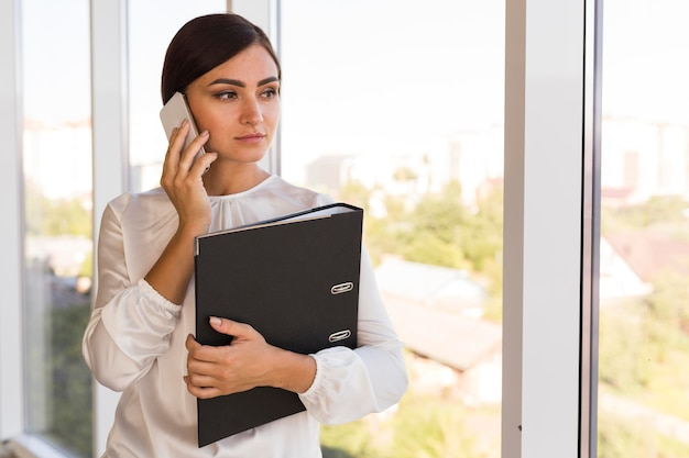 Vista frontal da empresária segurando a pasta e falando ao telefone