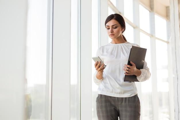 Vista frontal da empresária segurando a pasta e olhando para o smartphone