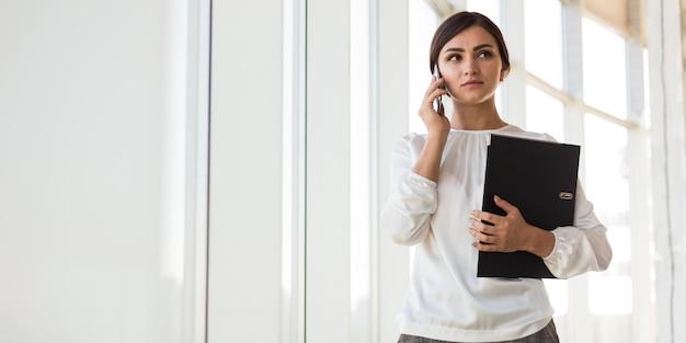 Vista frontal da empresária segurando a pasta enquanto fala ao telefone
