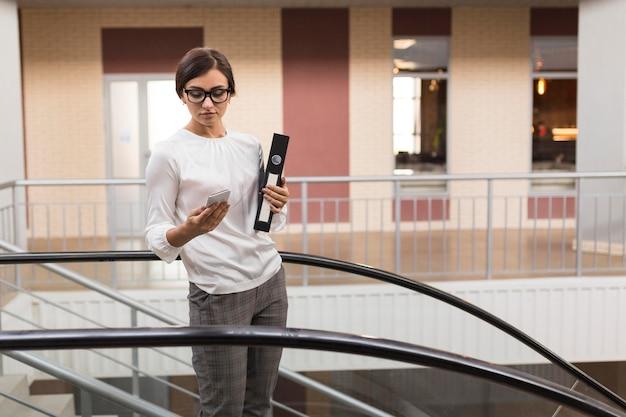 Vista frontal da empresária segurando fichário e smartphone na escada rolante