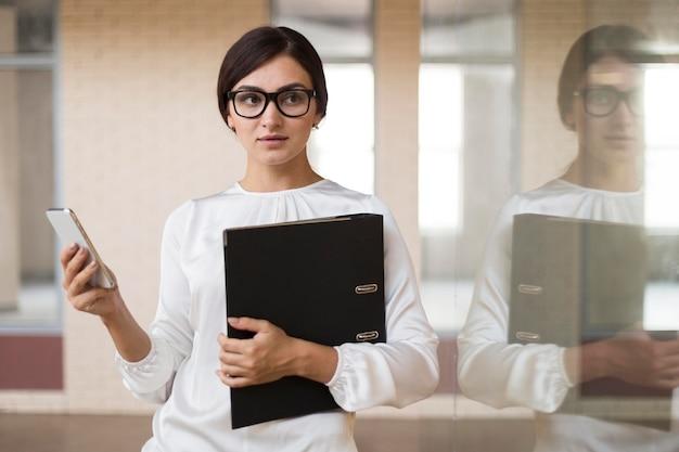 Vista frontal da empresária segurando o smartphone e a pasta