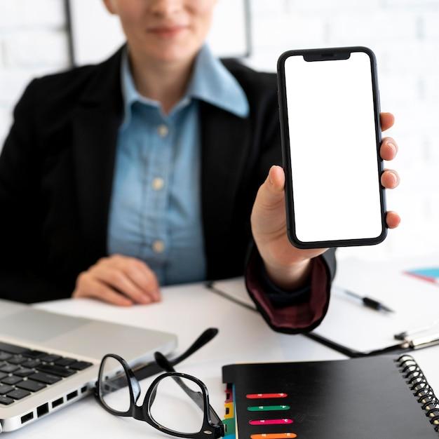 Vista frontal da empresária segurando o smartphone no escritório