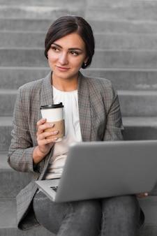 Vista frontal da empresária tomando café e trabalhando no laptop nas escadas