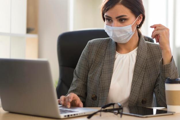 Vista frontal da empresária trabalhando com máscara facial na mesa