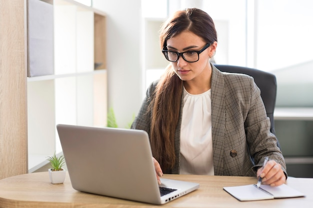 Vista frontal da empresária trabalhando em um laptop no escritório