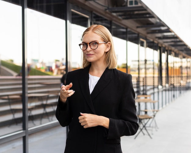 Vista frontal da empresária usando linguagem de sinais ao ar livre no trabalho