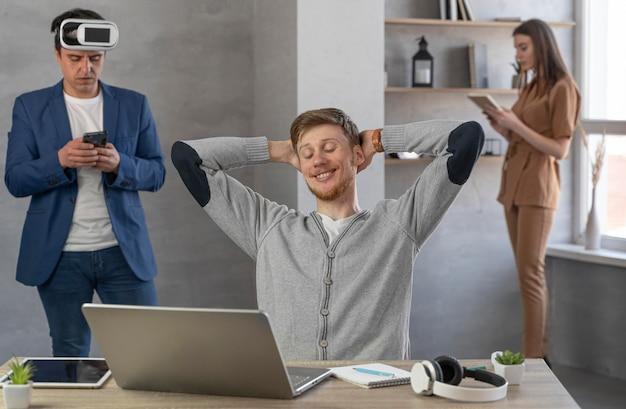 Vista frontal da equipe de jovens usando laptop e fone de ouvido de realidade virtual