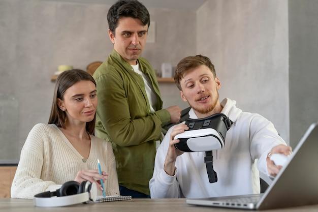 Vista frontal da equipe de pessoas usando laptop e fone de ouvido de realidade virtual
