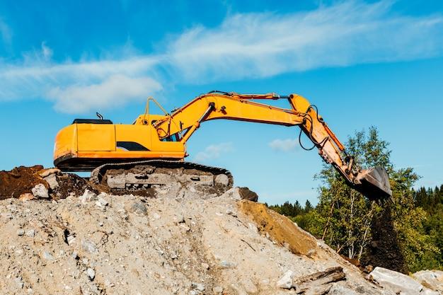 Vista frontal da escavadeira sobre esteiras escavando no local de demolição