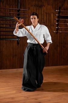 Vista frontal da estagiária de artes marciais na sala de prática