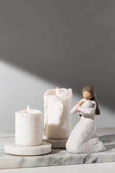 Vista frontal da estatueta feminina do dia da epifania com velas